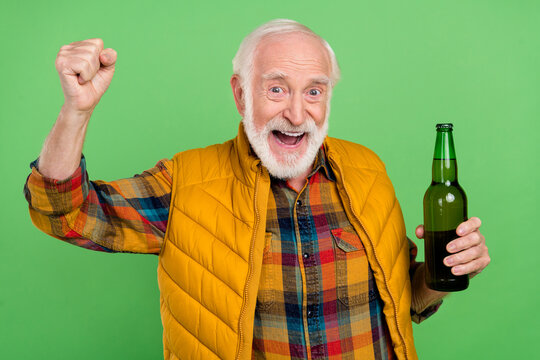 Photo of charming lucky senior gentleman wear yellow vest rising fist drinking beer smiling isolated green color background