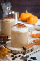 Obraz A glass of hot  autumn drink pumpkin spice latte in alternate healthy way without whip cream with mousse of milk topped with ground spices. Jack-Be-Little squad in background, with coffee bean - fototapety do salonu