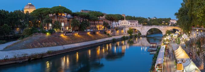 Rome - The Isola Tiberiana - Tiberian Island with the Ponte Cestio bridge at dusk.