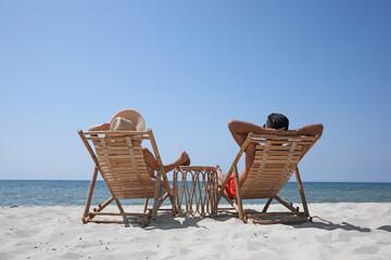 Obraz Couple resting in wooden sunbeds on tropical beach - fototapety do salonu