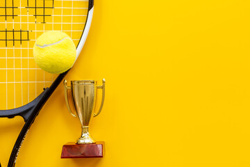 Obraz Small golden trophy cup with tennis racket and ball. Sport champion winner concept - fototapety do salonu
