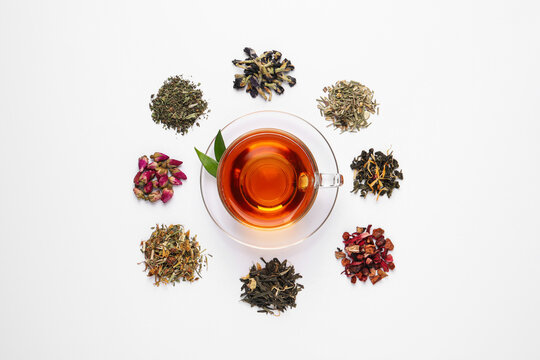 Composition with brewed tea, dry and fresh leaves on white background, top view