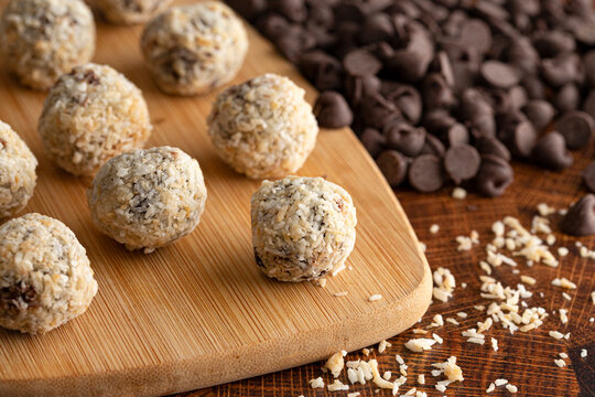 Group of Coconut Chocolate Energy Balls on a Wooden Butcher Block