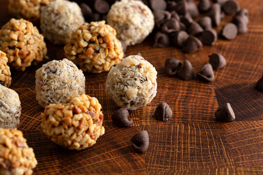 Group of Peanut Butter and Coconut Chocolate Energy Balls on a Wooden Butcher Block
