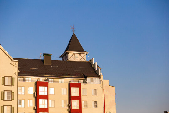 German weather vane on the roof of a colored building against the background of the sky