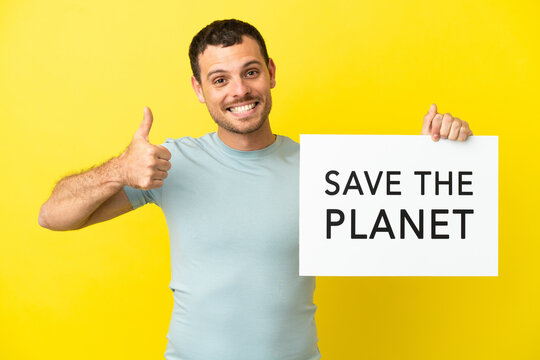 Brazilian man over isolated purple background holding a placard with text Save the Planet with thumb up