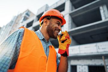 Obraz Young construction worker in uniform using walkie talkie on site - fototapety do salonu