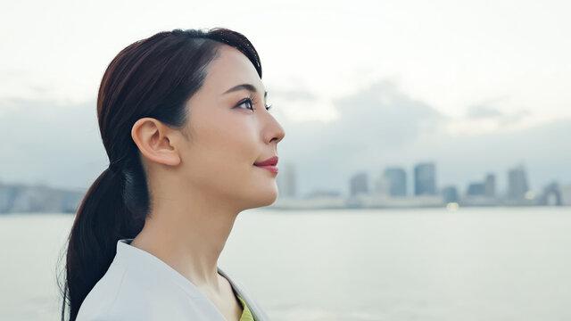 都市の前で遠くを見つめる女性