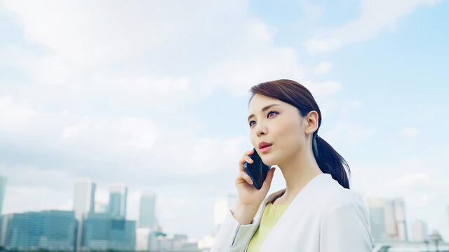 都市を背景にスマホで通話する女性