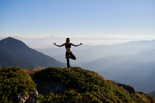 Front view of young attractive woman doing meditation on fresh air in the morning with beautiful landscape. Concept of meditation.