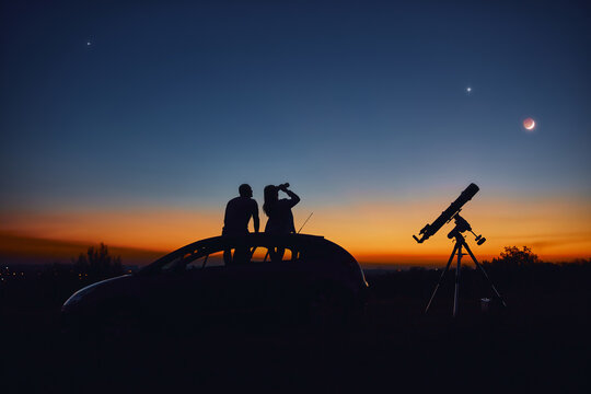 Couple stargazing together with a astronomical telescope.