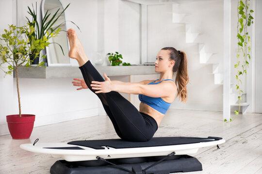 Young woman athlete performing a Navasana or yoga Boat Pose