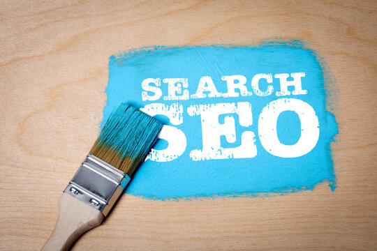 Search, SEO concept. Blue paint and paint brush on a wooden surface