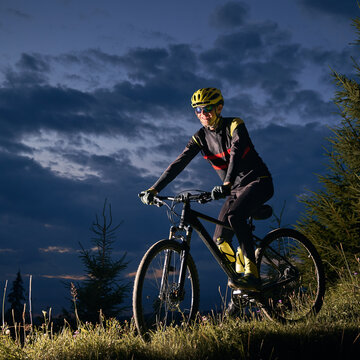 Smiling young man riding bicycle downhill with beautiful blue evening sky on background. Male bicyclist cycling down grassy hill at night. Concept of sport, biking and active leisure.