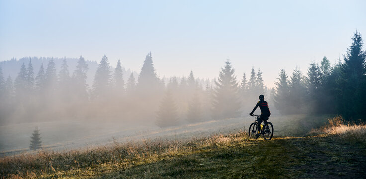 Man cyclist riding his bicycle in the mountains in early foggy morning. Sun beams get through wall of evergreen spruces and enlight rider. Concept of active lifestyle and mountains ride