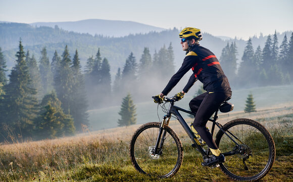 Man bicyclist riding his bicycle in the mountains in early foggy morning. Side view of cyclist riding down a hill against beautiful landscape. Copy space. Concept of extreme sport