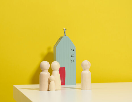 wooden family figurines, model house on a yellow background. Real estate purchase, rental concept. Moving to new apartments