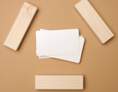 stack of white rectangular business cards on a brown background, company branding, address. View from above, flat lay