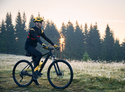 Side view of cyclist standing with bike on mountain trail with coniferous trees on background. Man bicyclist enjoying bicycle ride in mountains in the morning. Concept of sport and active leisure.