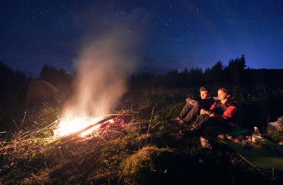 Horizontal snapshot of couple of tourists spending time together in camping. Young boy and girl near campfire in the evening outdoors in nature.