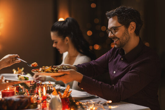 holidays, party and celebration concept - happy man with friends having christmas dinner at home