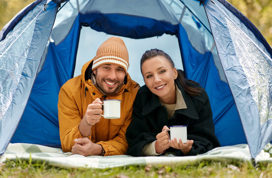 camping, tourism and travel concept - happy couple lying inside tent and drinking tea at campsite