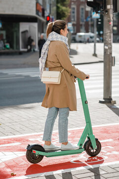 traffic, city transport and people concept - woman riding electric scooter along red bike lane with signs of bicycles and two way arrows on street