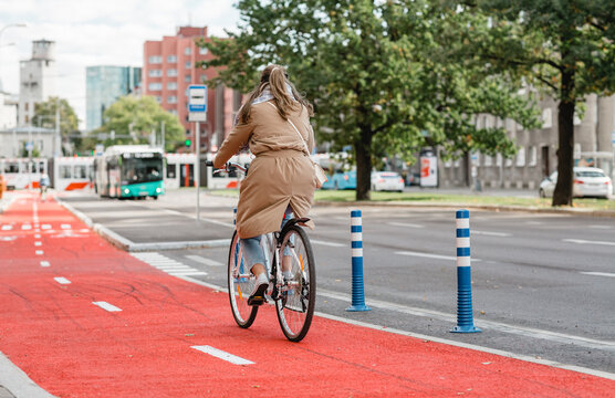 traffic, city transport and people concept - woman riding bicycle along red bike lane or two way road on street