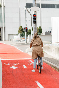 city transport and people concept - woman with bicycle waiting for green traffic light signal on red bike lane in tallinn, estonia