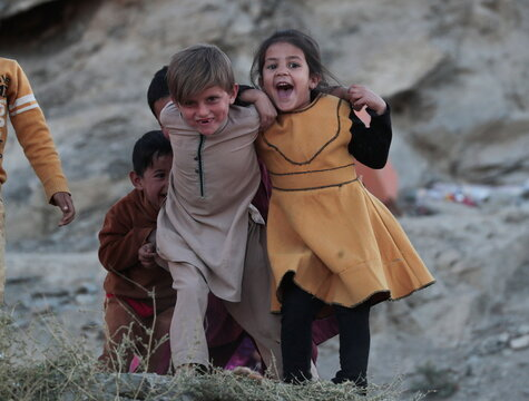 Children play outside their house at Tv mountain in Kabul