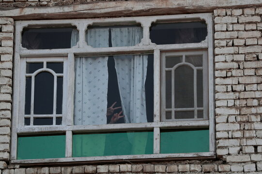 Samira, 15, and Sadaf, 13, flash the victory sign through a window in their house at Tv mountain in Kabul