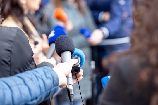 Journalists at news conference or media event, microphone in the focus