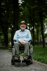 Obraz Adult disabled man in wheelchair holds paper sheet - fototapety do salonu
