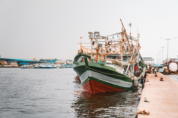 Obraz Fishing boat tied to a pier on a  gloomy day in Indonesia - fototapety do salonu