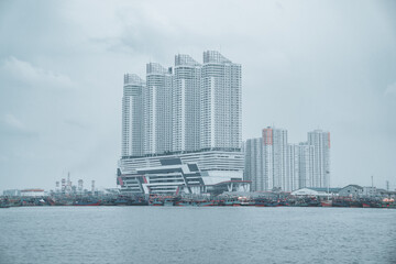 Obraz Beautiful view of tall skyscrapers on the seashore in Jakarta city, Indonesia on a gloomy day - fototapety do salonu