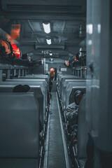 Obraz Vertical shot of a narrow train passageway between seats - fototapety do salonu