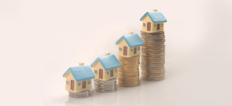 Model of detached miniature house mock up on coins