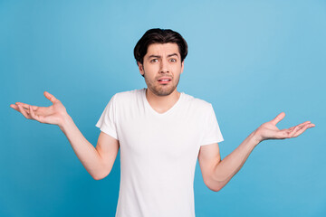 Fototapeta Photo of unsure troubled guy shrug shoulders confused face wear white t-shirt isolated blue color background obraz