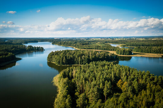 Aerial view of green islands and clouds at summer sunny day. Masurian Lake District in Poland.