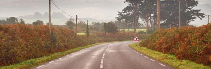 Obraz An empty highway with a sharp turn through the forest and hills at sunrise. Brittany, France. Morning fog. Autumn colors. Picturesque scenery. Travel destinations, freedom, adventure, driving - fototapety do salonu