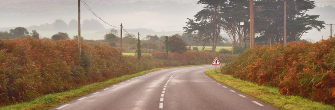 An empty highway with a sharp turn through the forest and hills at sunrise. Brittany, France. Morning fog. Autumn colors. Picturesque scenery. Travel destinations, freedom, adventure, driving