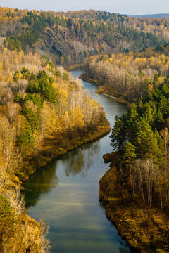 There is a beautiful place called Berdsk cliffs or Berdskie skaly in the Novosibirsk region. Rocks in these places are composed of igneous rocks. Top view of Berdsk river bend, autumn forest. Vertical