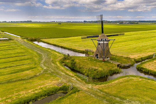 Old wooden windmill in green agricultural grassland