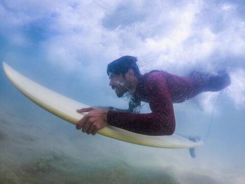 Surfer duck diving a wave