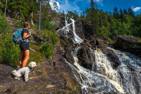 Elgafossen - Algafallet,  Backpacker girl with her dog looks at Waterfall Located between Sweden and Norway