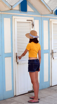 young girl  walks into the beach dressing room to wear a swimsuit