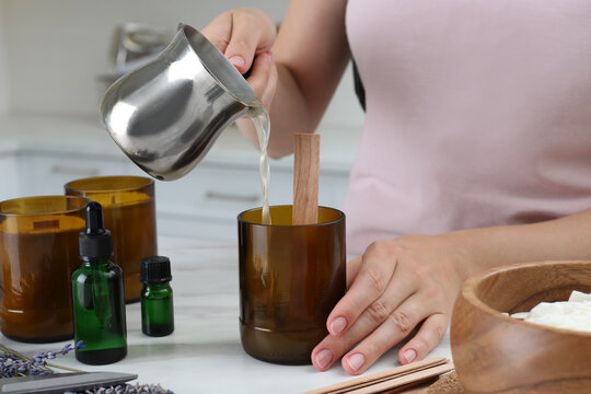 Woman making homemade candle at table in kitchen, closeup