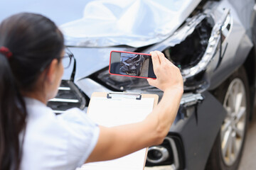 Obraz Insurance agent takes pictures of damage to car after accident on smartphone - fototapety do salonu