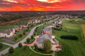 Obraz Aerial view of new construction winding dead-end street lined with luxury houses, large lots,  in upper class neighborhood American real estate development in the USA with stunning sunset orange sky - fototapety do salonu