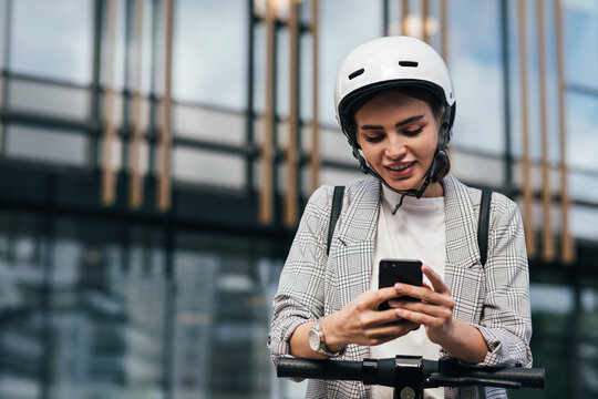 Woman in formal wear typing on smartphone while leaning on the handlebar of electric scooter while standing at an office building